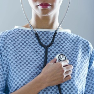 Female patient holding stethoscope to chest (Tetra Images)